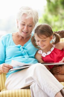42257780 - grandmother and granddaughter reading book on garden seat